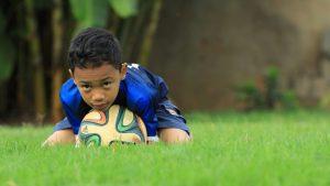 Jongen klemt voetbal vast