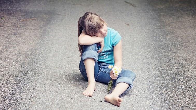 Meisje zit alleen, met bosje veldbloemen in haar hand