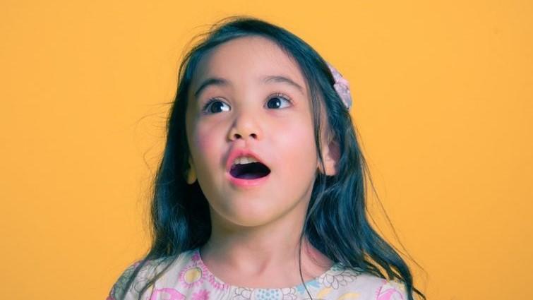 Meisje tegen oranje achtergrond dat verbazing uitdrukt