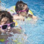 peuters in het zwembad met zwembandjes om en zonnebrillen op