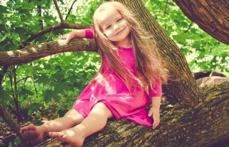 Eigenwijd kijkend meisje in een boom
