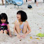 2 kinderen met hun voeten in het zand