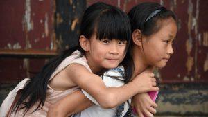 Chinees meisje met zusje op haar rug