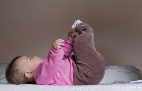 baby op de rug liggend, reikend naar voetje