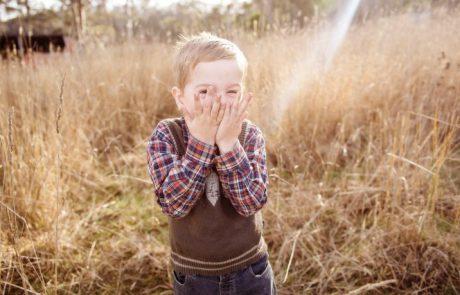 Jongetje met zijn handen voor zijn mond