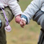 baby's die elkaar een handje geven op de arm van hun ouders