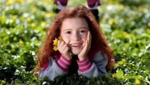 vrolijk meisje liggend in het gras