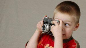 Jongetje kijkt door lens fotocamera