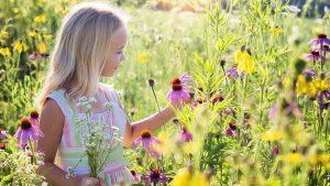 Meisje in veld met wilde bloemen