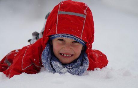 lachend kind liggend in de sneeuw